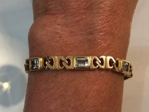 14k gold and blue topaz on wrist